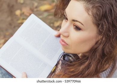 Beautiful girl with a book in the park. Reading book cute woman with curly long red hair, resting in an autumn park.