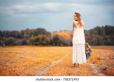 Beautiful girl with a bouquet of blue flowers on nature in autumn