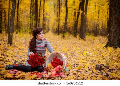 beautiful girl with a bouquet of chrysanthemums in autumn forest