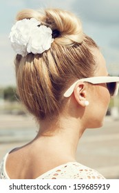 Beautiful girl with bow coiffure. Back view. Outdoors.