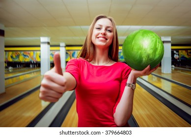 Beautiful girl at the bowling alley with the ball