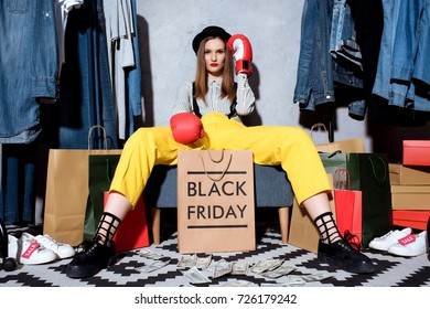 beautiful girl in boxing gloves with shopping bags and clothes around, black friday concept