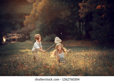 Beautiful girl and boy are catching butterflies with their butterfly net. Image with selective focus and toning