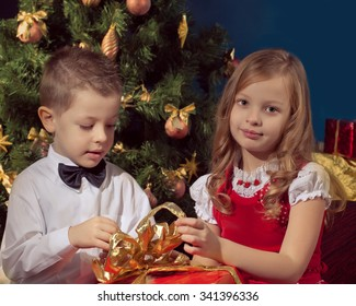 beautiful girl  and boy holding gifts near  Christmas tree