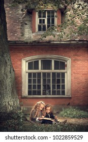 Beautiful girl and boy are reading a book under the autumn tree near a old house. Vertical image with selective focus and toning