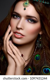 Beautiful girl with bright make-up, jewelery peacock feather earrings, diadem and manicure. Sensual east look