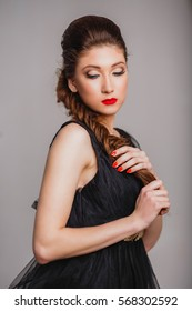 beautiful girl with bright makeup red lips in black dress with pigtails looking down on a light background