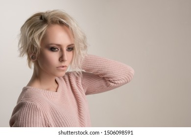A beautiful girl with bright makeup and short white hair stands in a half-turn on a white background and looks in front of her