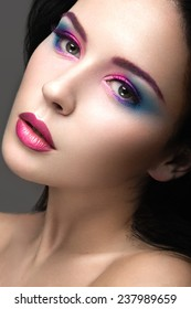 Beautiful girl with bright pink make-up and perfect skin. Beauty face. Festive image. Picture taken in the studio on a gray background.