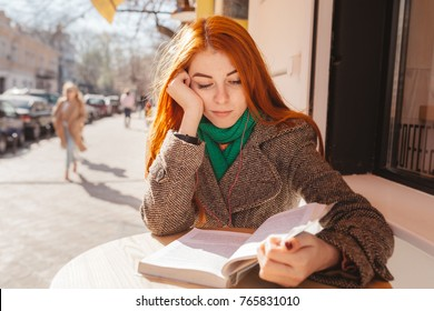 a beautiful girl with a bright red hair is reading a book at a table in a cafe and propping her head with her hand and listening to music in a pink earpiece