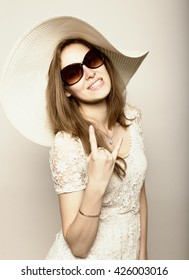 beautiful girl in broad-brimmed hat and sunglasses posing and expresses different emotions