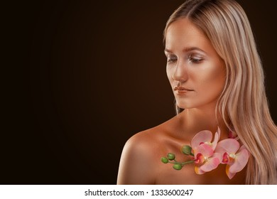 Beautiful girl with bronze skin. Golden shining makeup with orchid on the dark background