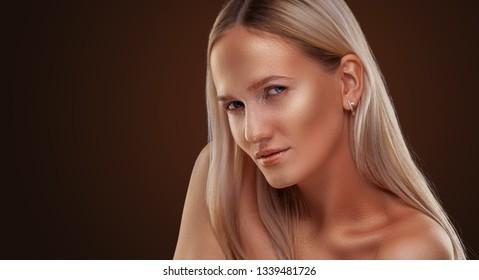Beautiful girl with bronze skin. Golden shining makeup on the dark background
