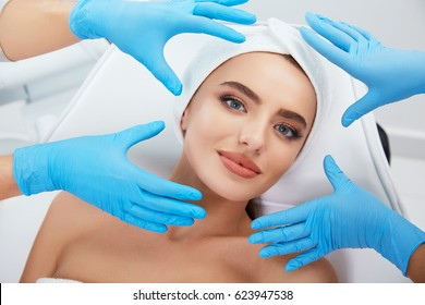 Beautiful girl with brown hair fixed behind,clean fresh skin naked shoulders wearing white bath robe and hair bandage, doing cosmetic procedure, doctors  hands wearing medical gloves near face.