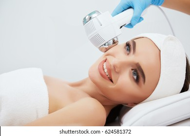 Beautiful girl with brown hair fixed behind,clean fresh skin naked shoulders wearing white bath robe and hair bandage, doing cosmetic procedure at light medical background, spa tool.