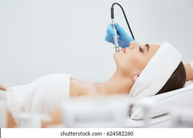 Beautiful girl with brown hair fixed behind,clean fresh skin naked shoulders wearing white bath robe and hair bandage, doing cosmetic procedure at light medical background, microdermabrasion.