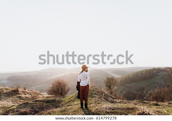 Beautiful girl in brown pants and with a hat walks to mountain places with a young spring grass. traveler hipster is holding hat in sunset. travel concept. View from behind