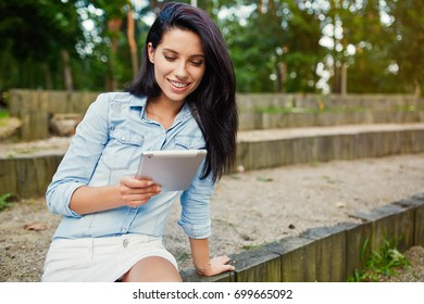 Beautiful girl browsing the internet on the tablet