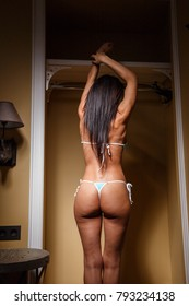 Beautiful girl brunette sexy fitness lingerie swimsuit posing in the room in the interior
