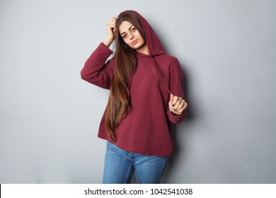 Beautiful girl in burgundy hoodie on a dark background with long hair. Mock-Up