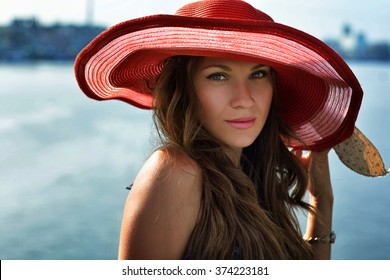 Beautiful girl (business woman) in a red hat smiling at the summer waterfront