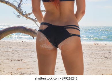 Beautiful girl butt in stylish bikini on tropical sandy beach
