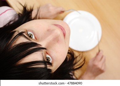 Beautiful girl with by empty plate at the table looking upwards