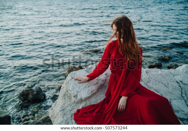 Beautiful girl by the sea. A woman in a red dress on the beach. Maritime vacation. Journey to the sea