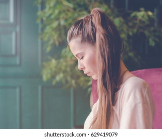 Beautiful girl in cafe, look away with sad pained expression. Young charming woman thinking about new ideas, drink a coffee, sitting on a lilac armchair in a modern city bar.