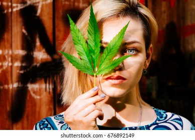 Beautiful girl with a cannabis leaf near the face