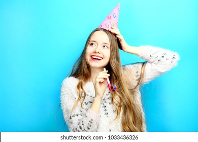 Beautiful girl in a cap and with a pipe on a blue background. Concept birthday.