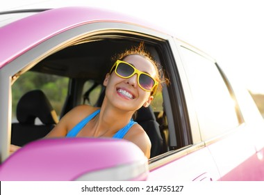 Beautiful girl in a car smiling in pink sunglasses