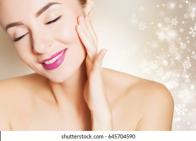 beautiful girl cares of her face, background with snowflakes