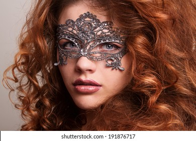 Beautiful Girl in a Carnival mask. Masquerade. Beauty portrait redhead girls.Girl with lush hair.Ginger hair.Woman with voluminous hair
