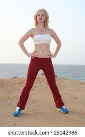 Beautiful girl carries out sports exercises on a sea coast