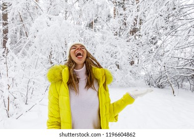 a beautiful girl catches a mouth with snowflakes in the woods in winter, and on her is a yellow down jacket and a white hat