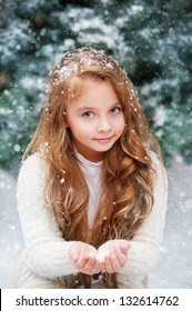 Beautiful girl catches snowflakes