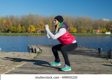 A beautiful girl (caucasian white) with a slim figure in the black leggings and bright pink jacket do sports in the autumn park in sunny weather. woman fitness jogging workout wellness concept.