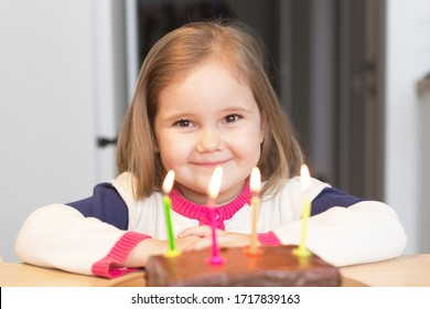 Beautiful girl celebrates four years. Happy childhood. Portrait. In front of the girl is a cake with candles. Selective focus. Bright interior on the background.