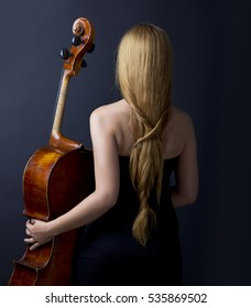 Beautiful girl with cello on the black background. Beautiful musician.