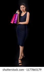 Beautiful girl with charm face holding shopping bags. With black background.