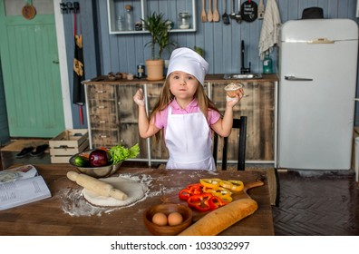 beautiful girl in a chef suit is crooked in the kitchen