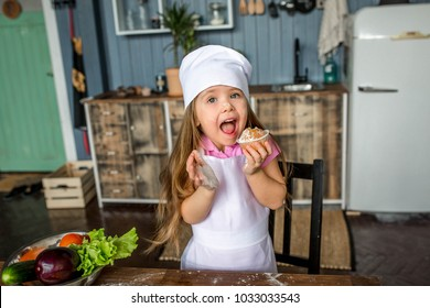 beautiful girl in a chef suit eating a cupcake in the kitchen