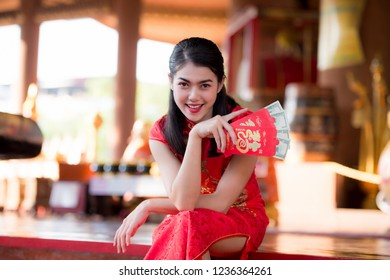 beautiful girl in the Cheongsam red dress up open the red envelope with money, in the Chinese New Year. Festivities, New Year Celebration