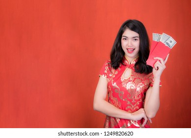 beautiful girl in the Cheongsam red dress up open the red envelope with money on red background, in the Chinese New Year. Festivities, New Year Celebration