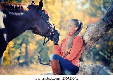 Beautiful girl with chestnut horse in autumn forest. Toned image
