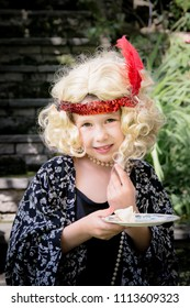 Beautiful Girl Child Dressed Up as 1920s Flapper Girl with Wig, Pearls & Feather Headband at British Tea Party