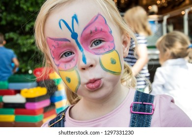 beautiful girl at a children's party with butterfly drawing on face