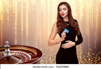 beautiful girl with chips stands on the background of roulette.