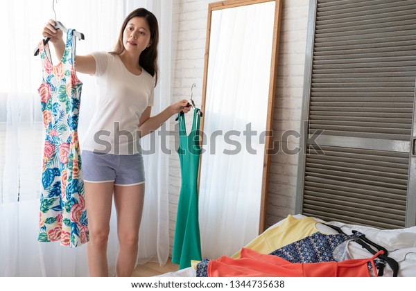 Beautiful girl choose dress what to wear near mirror standing on wooden floor. joyful woman holding cloth hanger looking for today outfit at home in the morning. elegant female picking for date.